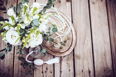 Vintage huwelijk decor, parfum en parel kralen, boeket van bloemen en kaarsen op een dienblad
