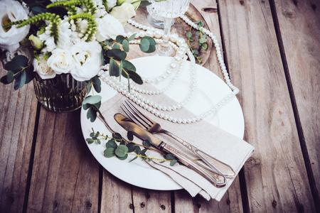 ビンテージのウェディング テーブルの装飾、食器、パールビーズ、花の花束と古い木製ボード上のワイングラス
