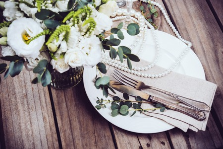 wine glasses: Vintage wedding table decor, tableware and pearl beads, flower bouquet and wine glasses on an old wooden board