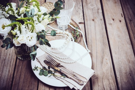 Vintage wedding table decor, tableware and pearl beads, flower bouquet and wine glasses on an old wooden board