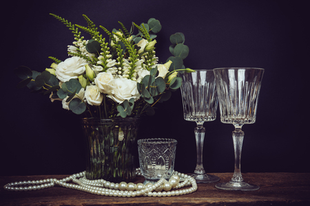 wine glasses: Beautiful bouquet of white flowers, pearl beads and wine glasses on an old wooden board on a black chalkboard background