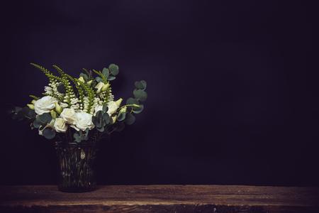 rosas blancas: Hermoso ramo de flores blancas en un florero en un tablero de madera sobre un fondo negro pizarra