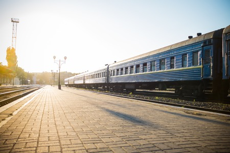 chernivtsi: Railway platform and a train in the sun backlight, travel background