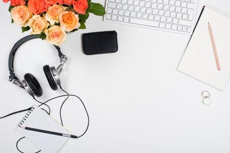 장미, 컴퓨터 키보드, 헤드폰 및 흰색 배경에 메모장 여성 책상 작업 영역. 시작 개념, 톱보기 mockup입니다. 스톡 콘텐츠