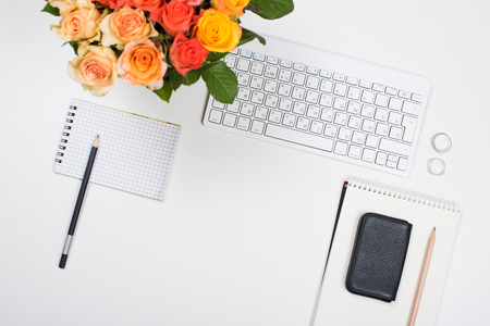 yellow notepad: Feminine startup concept, office desk workspace with roses, computer keyboard and notepad on white background. Hipster style mockup.