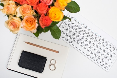 empty office: Feminine startup concept, office desk workspace with roses, computer keyboard and notepad on white background. Hipster style mockup.