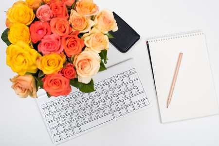 feminine: Feminine startup concept, office desk workspace with roses, computer keyboard and notepad on white background. Hipster style mockup.