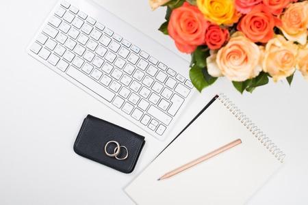 arreglo floral: concepto de inicio femenino, oficina de área de trabajo de escritorio con las rosas, el teclado del ordenador y el bloc de notas en el fondo blanco. maqueta estilo inconformista.