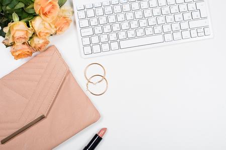 Modello di area di lavoro femminile ufficio con fiori, borsa, rossetto beige, tastiera e blocco note su sfondo bianco. Archivio Fotografico