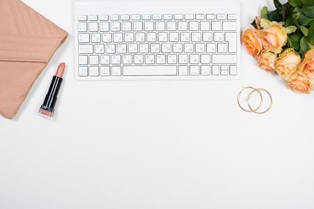 Vrouwelijke bureau werkruimte mockup met bloemen, handtas, beige lippenstift, toetsenbord en notitieblok op een witte achtergrond.