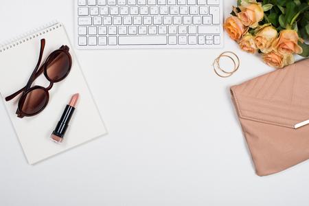 흰색 배경에 꽃, 핸드백, 베이지 색 립스틱, 키보드 및 메모장 여성 사무실 책상 작업 공간 모형. 스톡 콘텐츠