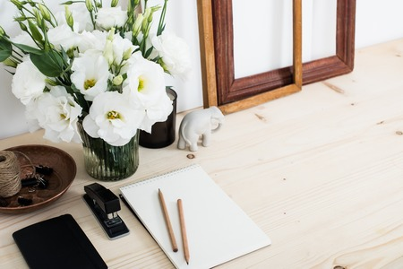 home office interior: White contemporary feminine work desk with flowers, art frames and notepad, home office interior closeup