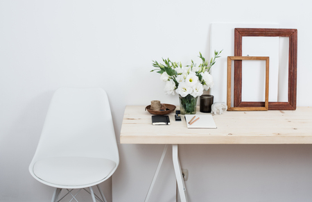 Stijlvol Scandinavisch interieur, wit werkruimte met bureau en stoel, trendy kunstenaar studio decor.