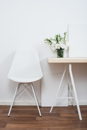 White scandinavian interior decor closeup: empty walls, designer chair, table and natural flowers. Stock Photo