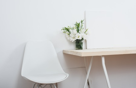 arrangements: White scandinavian interior decor closeup: empty walls, designer chair, table and natural flowers. Stock Photo