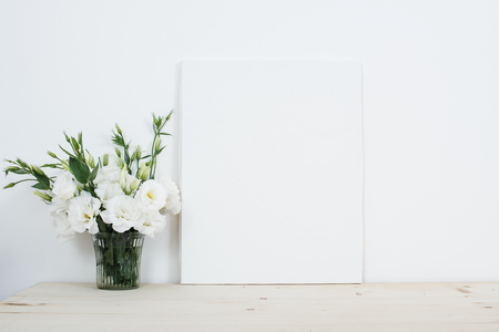 White interior decor, fresh natural flowers in vase and empty canvas on table Stockfoto