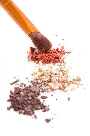 Makeup brushes set and loose powder eyeshadows isolated on white background,  cosmetic tools macro shot