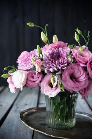 arreglo floral: Ramo de flores de color rosa en un florero, eustoma y el crisantemo, elegante decoración casera rústica de la vendimia