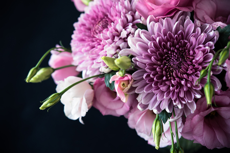 Bouquet of pink flowers closeup on black background, eustoma and chrysanthemum, elegant vintage floral decor Banco de Imagens