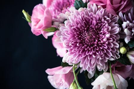 Bouquet di fiori rosa alzato su sfondo nero, Eustoma e crisantemo, elegante decorazione floreale epoca