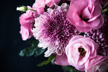Bouquet of pink flowers closeup on black background, eustoma and chrysanthemum, elegant vintage floral decor Stockfoto