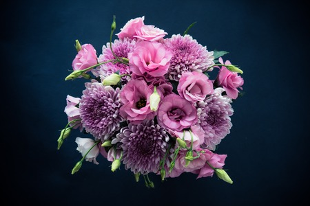 Bouquet of pink flowers closeup on black background, eustoma and chrysanthemum, elegant vintage floral decor, top view