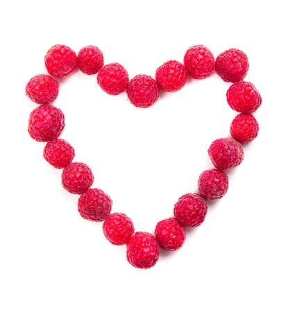 summer fruits: Fresh ripe raspberries heart shaped macro shot on white background isolated, love and fruit concept