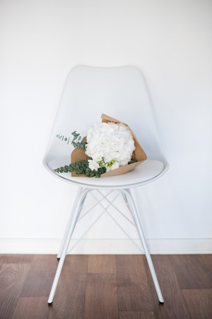 selebration: Bouquet of white hydrangeas on a chair by the wall Stock Photo