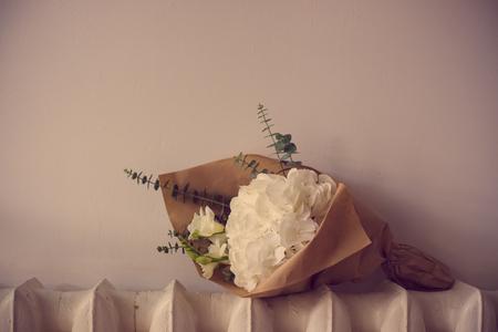 flower arrangement: Bouquet of white hydrangeas on the heating radiator, vintage style
