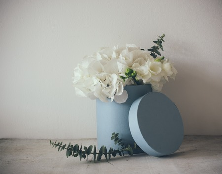 selebration: Bouquet of white hydrangeas in round blue box, vintage postcard style