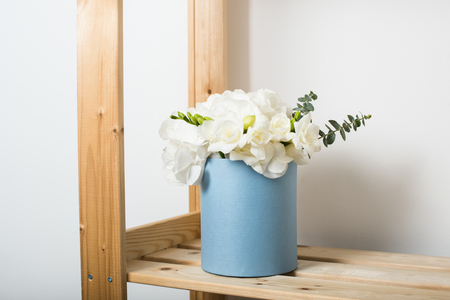 selebration: Bouquet of white hydrangeas in round  blue box on wooden shelf. Home interior decoration Stock Photo