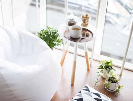 bean bag: Coffee served on table in bright light scandinavian style hipster interior, cozy loft room with large windows closeup Stock Photo