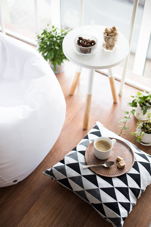 Coffee served on table in bright light scandinavian style hipster interior, cozy loft room with large windows closeup Foto de archivo