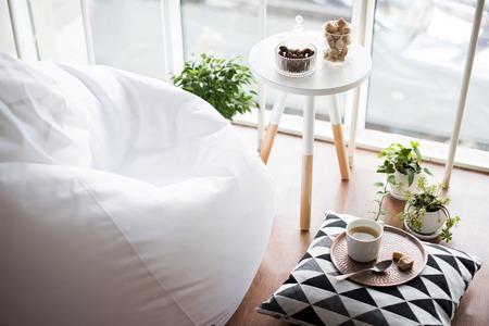 Caffè servito sul tavolo in brillante luce scandinavo stile pantaloni a vita bassa interno, accogliente sala loft con ampie finestre primo piano