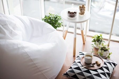 Coffee served on table in bright light scandinavian style hipster interior, cozy loft room with large windows closeup Stockfoto