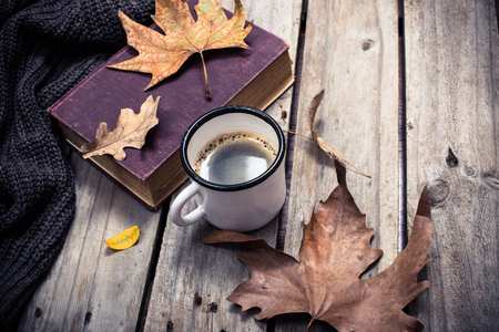 Old book, knitted sweater with autumn leaves and coffee mug on vintage wooden board background Stock Photo