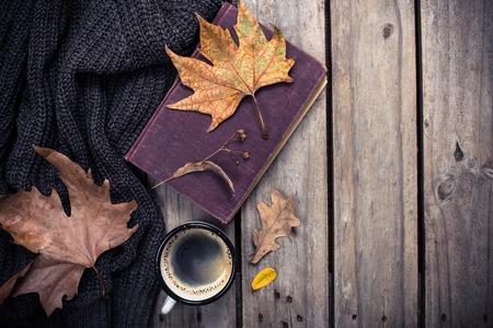 오래 된 책, 단풍 잎과 빈티지 나무 보드 배경에 커피 낯 짝을 짠된 스웨터 스톡 콘텐츠