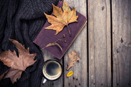 Old book, knitted sweater with autumn leaves and coffee mug on vintage wooden board background Foto de archivo
