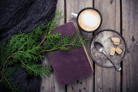 Cozy winter decoration, branch of spruce, warm sweater and a cup of coffee with sugar on old vintage wooden board