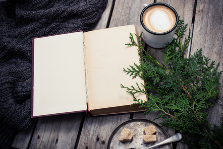 Cozy winter decoration, branch of spruce, warm sweater, ancient book and a cup of coffee with sugar on old vintage wooden board