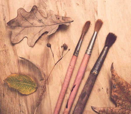 hojas antiguas: Four old used paintbrushes and autumn leaves on old wooden board background