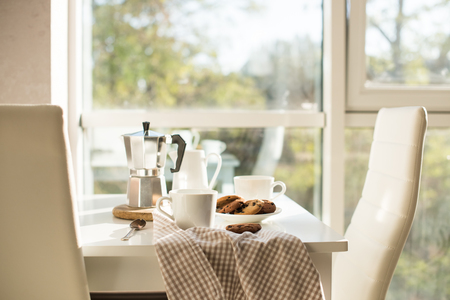이른 아침 프랑스어 홈 아침 식사, 커피, 밝은 햇빛에서 창 근처 테이블에 쿠키, 화이트 인테리어