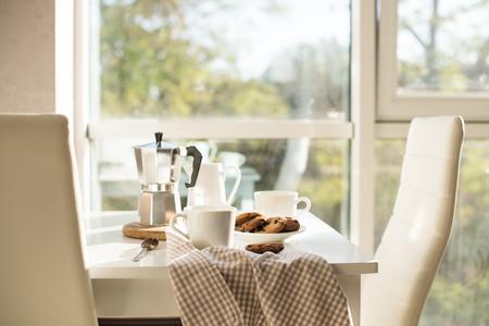 La mattina presto francese a casa la prima colazione, caffè e biscotti sul tavolo vicino a finestra in pieno sole, interno bianco