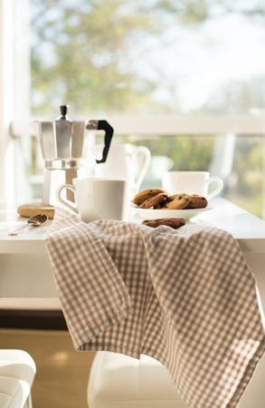 Ontbijt van de vroege ochtend het Franse huis, koffie en koekjes op de lijst dichtbij venster in helder zonlicht, wit binnenland Stockfoto