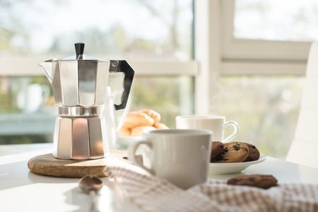 Vroeg in de ochtend frans huis ontbijt, koffie en koekjes op tafel in de buurt van venster in fel zonlicht, wit interieur