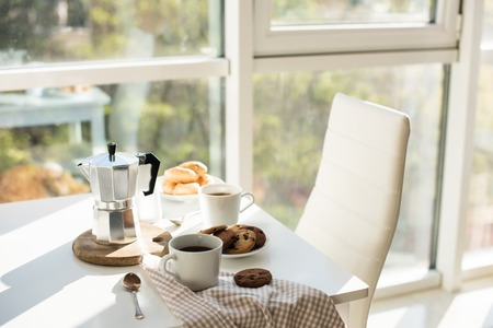 Early morning french home breakfast, coffee and cookies on the table near window in bright sunlight, white interior