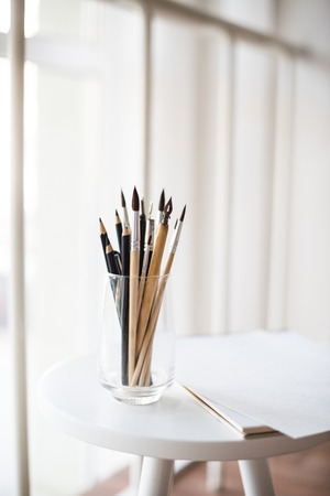 artistas: Creative artists workspace, artistic paint brushes and clean paper in studio interior, painting tools.