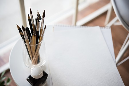 creative tools: Creative artists workspace, artistic paint brushes and clean paper in studio interior, painting tools.