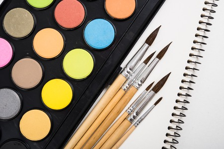 creative tools: Watercolor paint set and new brushes with clean paper on artists work desk, creative artistic tools isolated on white background closeup Stock Photo