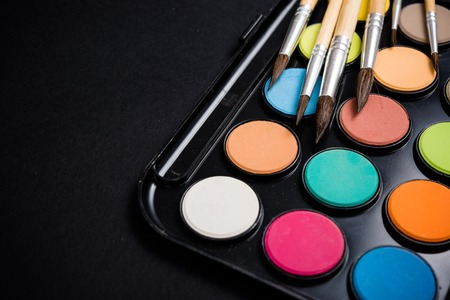 creative tools: New watercolor paint set and brushes on artists work desk, creative art tools isolated on black background closeup Stock Photo